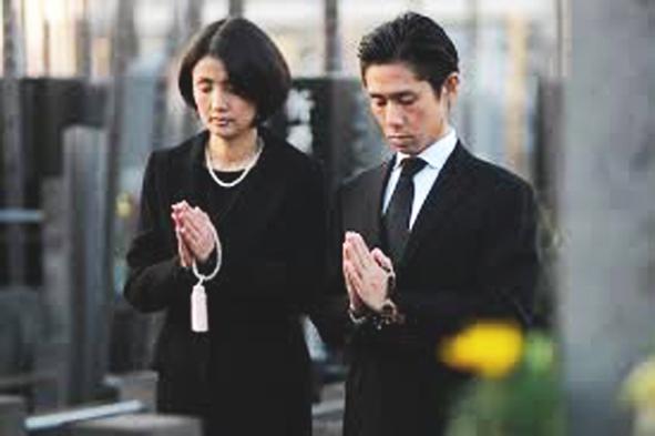 お墓の前で手を合わせている画像です。